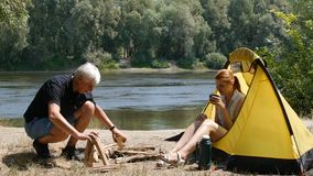 一个人在帐篷附近做火 少女观看他 旅游业,旅行,绿色旅游业概念 远足,旅行 股票视频