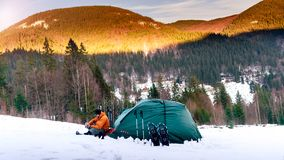 一个人在帐篷附近坐雪倒从热水瓶的茶 免版税库存照片