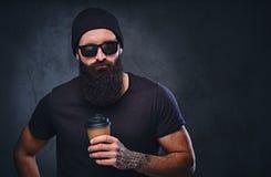 一个人在帽子和太阳镜举行拿走咖啡杯 库存照片