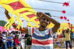 一个人在斯里兰卡帮助拿着在Negombo海滩的日本风筝 免版税库存照片