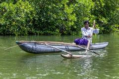 一个人在斯里兰卡用浆划一艘舷外浮舟 免版税图库摄影
