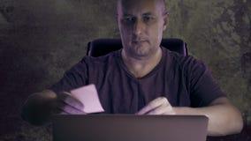 一个人在晚上在家工作在计算机 人黏贴了对笔记本屏幕的一个备忘录 一件T恤杉的一个人在黑暗 影视素材