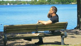一个人在晴朗天气的长凳在手机变冷并且镇静地谈话 股票视频