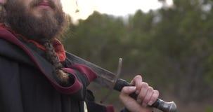 一个人在有一把剑的森林在他的肩膀看您 影视素材