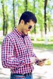 一个人在有一种片剂的一个公园站立在手、夏天玻璃和一件衬衣上在森林户外,读社交 图库摄影
