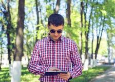 一个人在有一种片剂的一个公园站立在手、夏天玻璃和一件衬衣上在森林户外,读社交 免版税库存照片