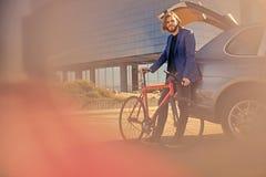 一个人在有开放树干的汽车附近拿着固定的自行车 库存照片
