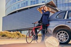 一个人在有开放树干的汽车附近拿着固定的自行车 图库摄影
