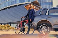 一个人在有开放树干的汽车附近拿着固定的自行车 免版税图库摄影