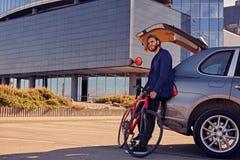 一个人在有开放树干的汽车附近拿着固定的自行车 免版税库存图片