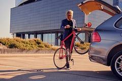 一个人在有开放树干的汽车附近拿着固定的自行车 免版税库存照片
