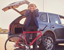 一个人在有开放树干的汽车附近拿着固定的自行车 库存图片