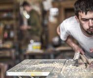 一个人在有木产品的机器工作 免版税库存照片