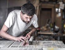 一个人在有木产品的机器工作 库存照片