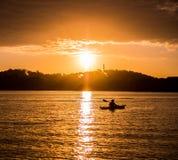 一个人在湖荡桨在日出 免版税库存照片