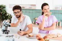 一个人在片剂收集机器人并且读某事 附近是他的女朋友和不满意吃三明治 库存图片