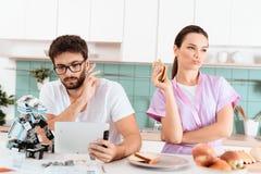 一个人在片剂收集机器人并且读某事 附近是他的女朋友和不满意吃三明治 库存照片