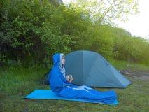 一个人在睡袋坐在帐篷附近 免版税库存照片