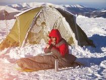一个人在睡袋坐在帐篷附近 库存照片