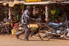 一个人在肯尼亚滚动自行车下来街道,人们 免版税库存图片