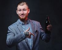 一个人在衣服举行穿戴了一个瓶用工艺啤酒 免版税库存照片