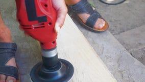 一个人在钻子的喷管帮助下擦亮委员会 与沙纸的铺沙的木木材 影视素材