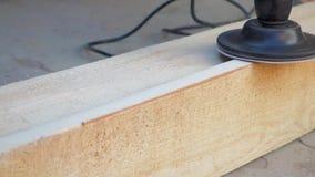 一个人在钻子的喷管帮助下擦亮委员会 与沙纸的铺沙的木木材 股票视频
