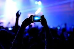一个人在活力地点拍与他的智能手机的一张照片在音乐会 图库摄影