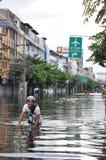 一个人在2011年10月乘坐他的在曼谷,泰国一条被充斥的街道的自行车水中, 库存照片