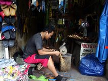 一个人在他的商店削尖一名顾客的一把锯 免版税图库摄影