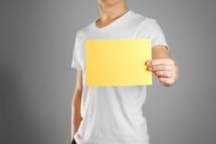 一个人在他的手上拿着一张黄色纸 显示一位空白的飞行物 库存图片
