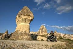一个人在Goreme附近在土耳其的卡帕多细亚地区骑通过一个神仙的烟囱的一辆方形字体自行车 免版税图库摄影
