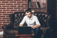 一个人坐一个豪华沙发并且在一台膝上型计算机后工作在他的书架的背景的办公室 图库摄影
