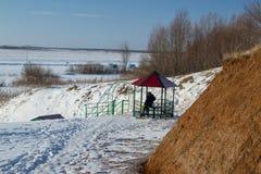 一个人坐一条冻河的河岸 免版税库存图片