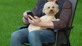 一个人坐与在他的胳膊的一条狗 股票录像