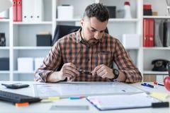 一个人坐在一张桌上在办公室并且看在一个磁性委员会的图表 库存照片