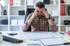 一个人坐在一张桌上在办公室并且看在一个磁性委员会的图表 免版税库存照片