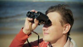 一个人坐在小船之外的海滩并且通过双筒望远镜看 股票录像