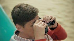 一个人坐在小船之外的海滩并且通过双筒望远镜看 影视素材