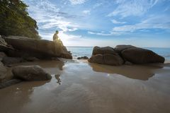 一个人坐在海滩的岩石 库存照片