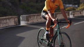 一个人坐在调查距离的一件黄色T恤杉和盔甲的一辆自行车站立在山路 股票录像