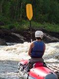 一个人坐穿戴救生衣和盔甲的筏 免版税库存图片