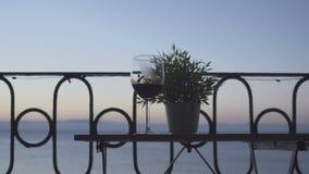 一个人坐阳台和饮用的红葡萄酒在海的背景 特写镜头 影视素材