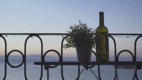 一个人坐阳台和饮用的红葡萄酒在海的背景 特写镜头 股票录像