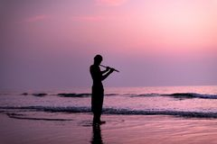 一个人实践演奏在桦树的长笛在日落 啊bizhyuteriya goa印度印第安最近的海运贸易妇女 16 01 2018年 库存图片