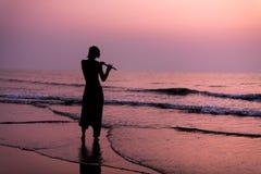 一个人实践演奏在海滩的长笛在日落 啊bizhyuteriya goa印度印第安最近的海运贸易妇女 16 01 2018年 免版税库存图片