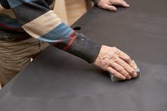 一个人对待黑表面无光泽的表面与与沙纸的一块海绵 免版税库存图片