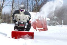 一个人工作雪吹的机器 库存图片