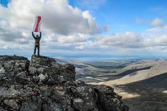 一个人征服了山的上面并且举行旗子飞行 免版税库存照片