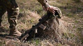 一个人战士的腿在干草的领域的伪装裤子打扮的投入地面机枪和 影视素材